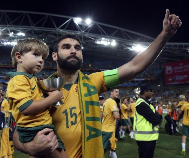 Australia's captain Mile Jedinak gestures while holding his child after they beat South Korea to win the Asian Cup at the Stadium Australia in Sydne